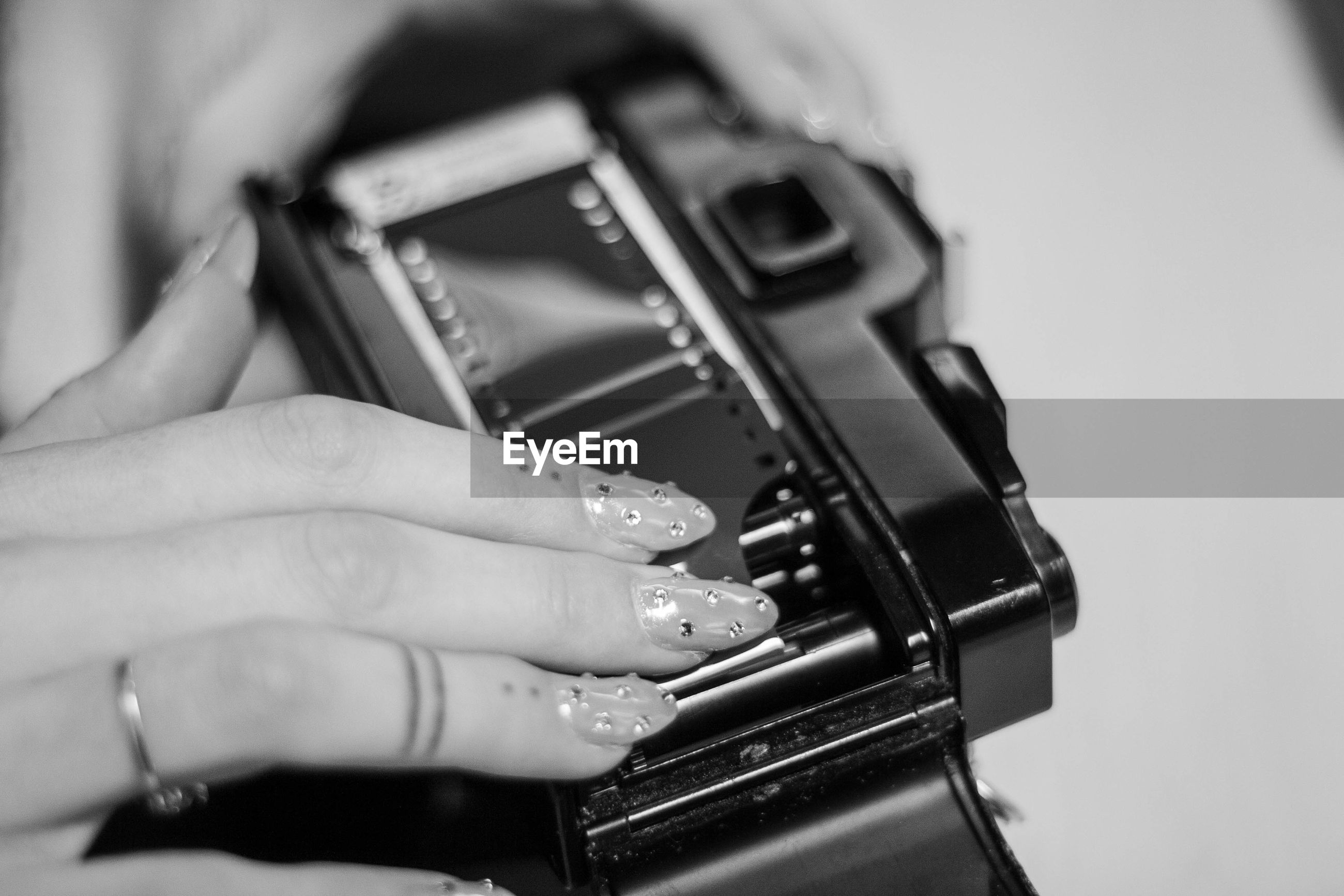 Cropped hand of woman touching vintage camera on table