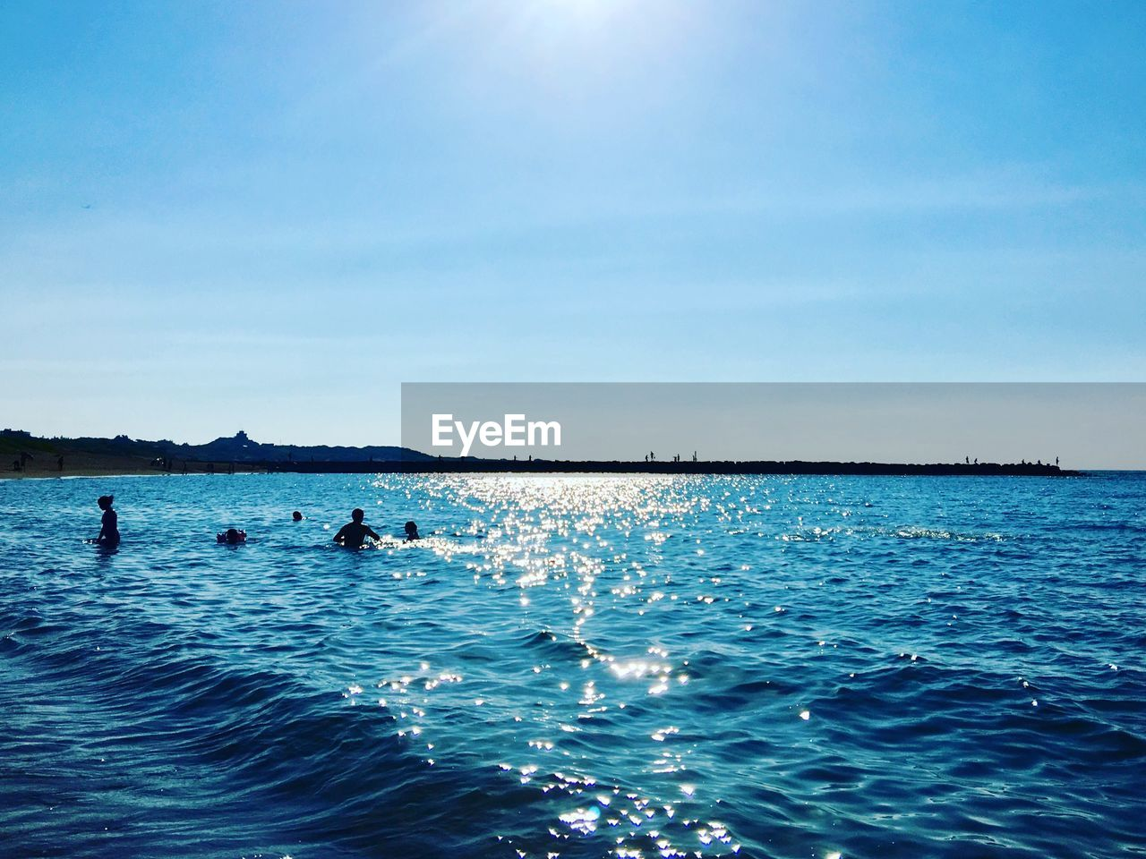 water, sky, sea, waterfront, scenics - nature, beauty in nature, nature, blue, day, rippled, sunlight, group of people, real people, tranquil scene, tranquility, unrecognizable person, non-urban scene, outdoors, nautical vessel
