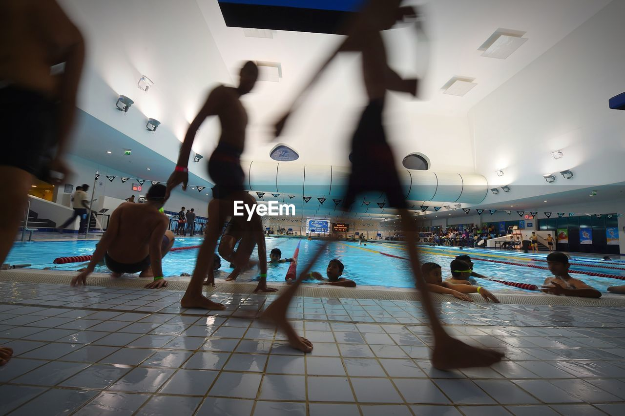 group of people, real people, blurred motion, large group of people, lifestyles, walking, motion, leisure activity, women, men, adult, crowd, indoors, flooring, architecture, day, tile, tiled floor, ceiling, swimming pool