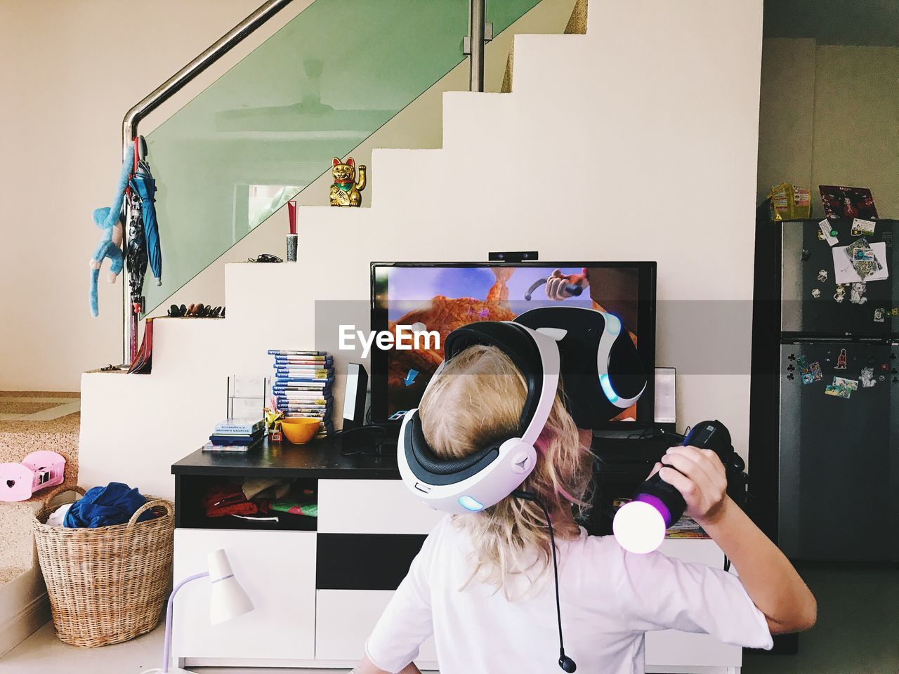 Rear view of girl playing with very simulator at home