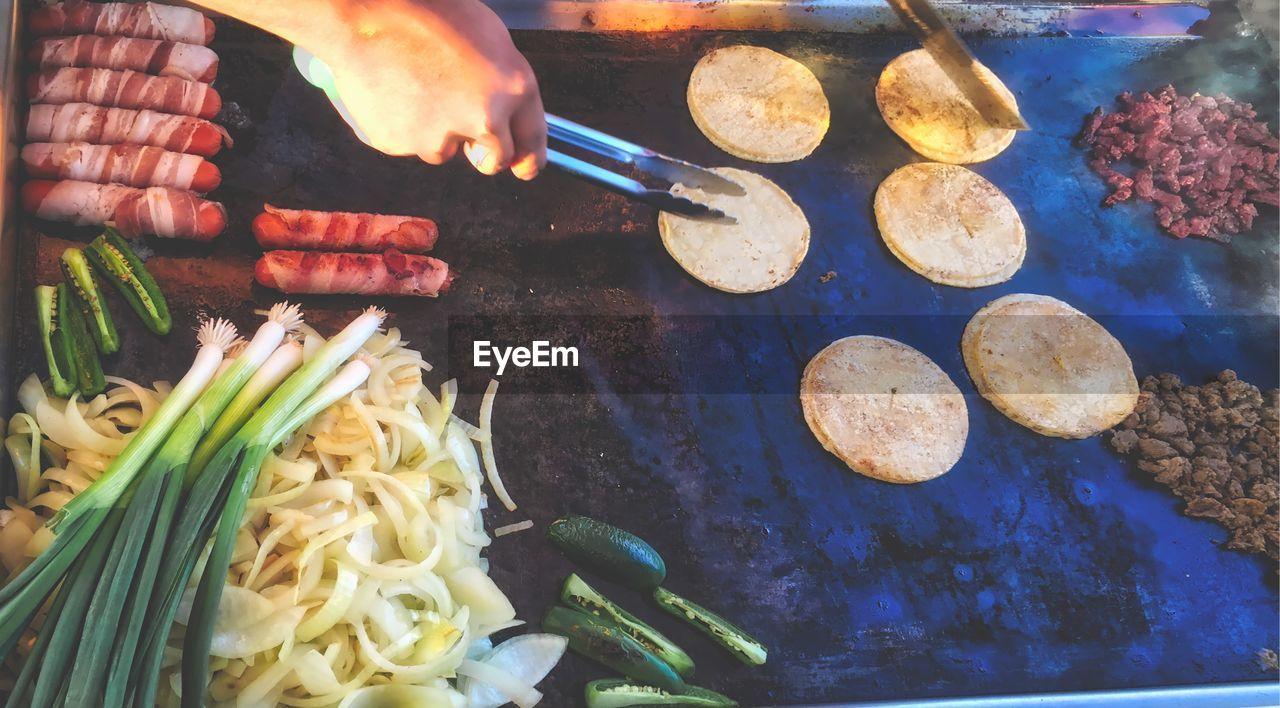 Cropped image of man preparing food on stove at street