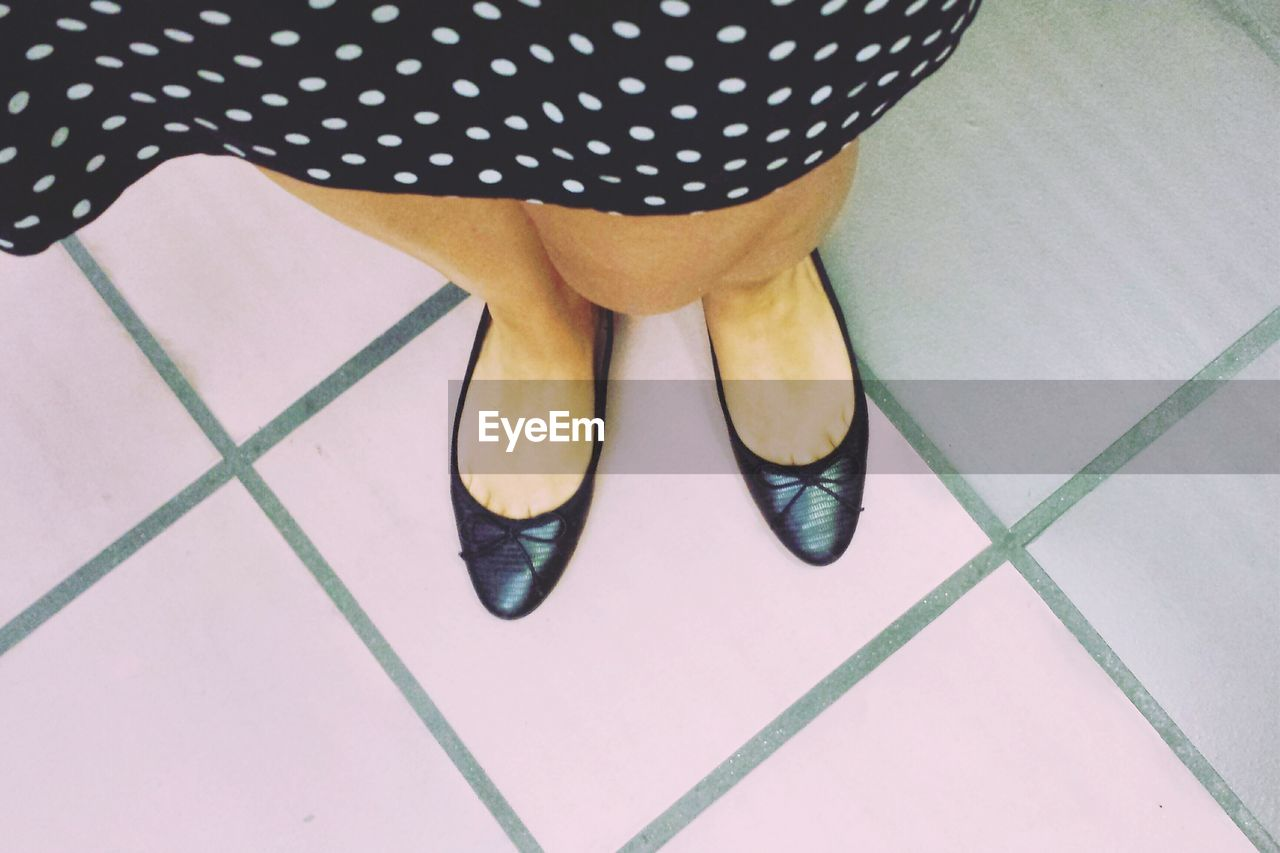 low section, human leg, polka dot, one person, real people, shoe, indoors, high angle view, standing, day, human body part, close-up, people