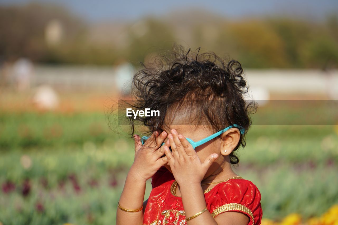 Close-up of girl covering eyes