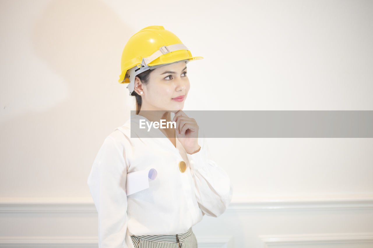 helmet, headwear, indoors, hardhat, one person, standing, yellow, hat, occupation, looking, protection, portrait, looking away, young adult, waist up, safety, security, real people
