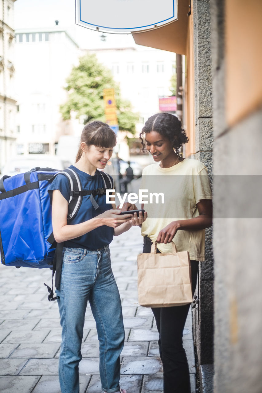 YOUNG WOMAN USING SMART PHONE WHILE STANDING ON CITY STREET