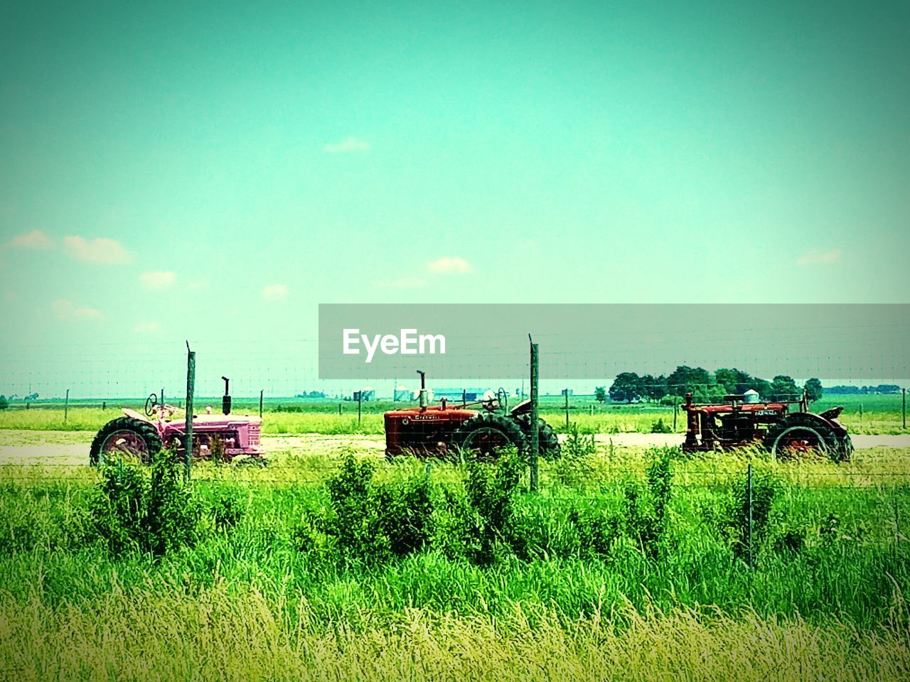 field, transportation, agriculture, agricultural machinery, tractor, farm, grass, growth, mode of transport, day, green color, land vehicle, rural scene, nature, combine harvester, outdoors, landscape, sky, no people, clear sky, stationary, scenics, plant, beauty in nature, nautical vessel