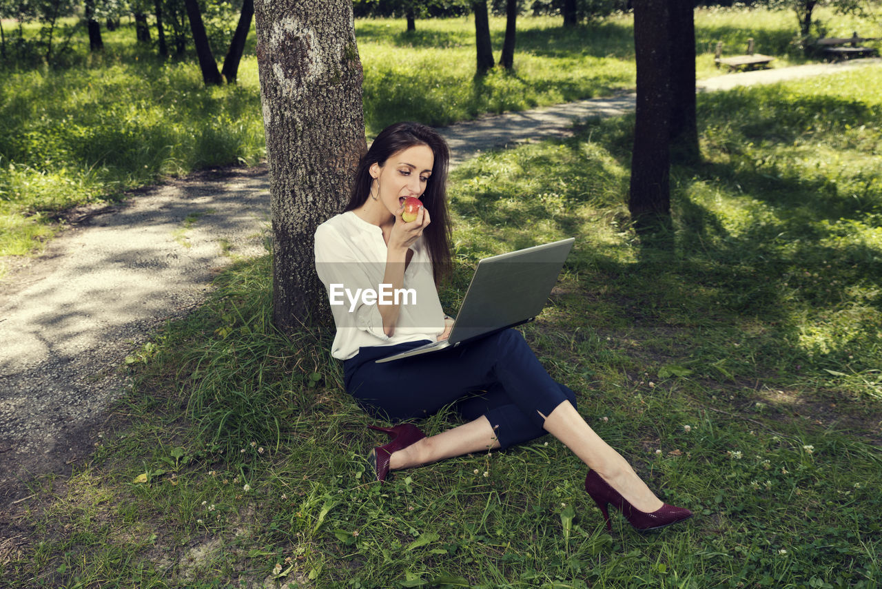 one person, plant, laptop, full length, real people, sitting, using laptop, computer, young adult, wireless technology, young women, technology, grass, tree, field, casual clothing, land, connection, adult, hairstyle, outdoors, beautiful woman