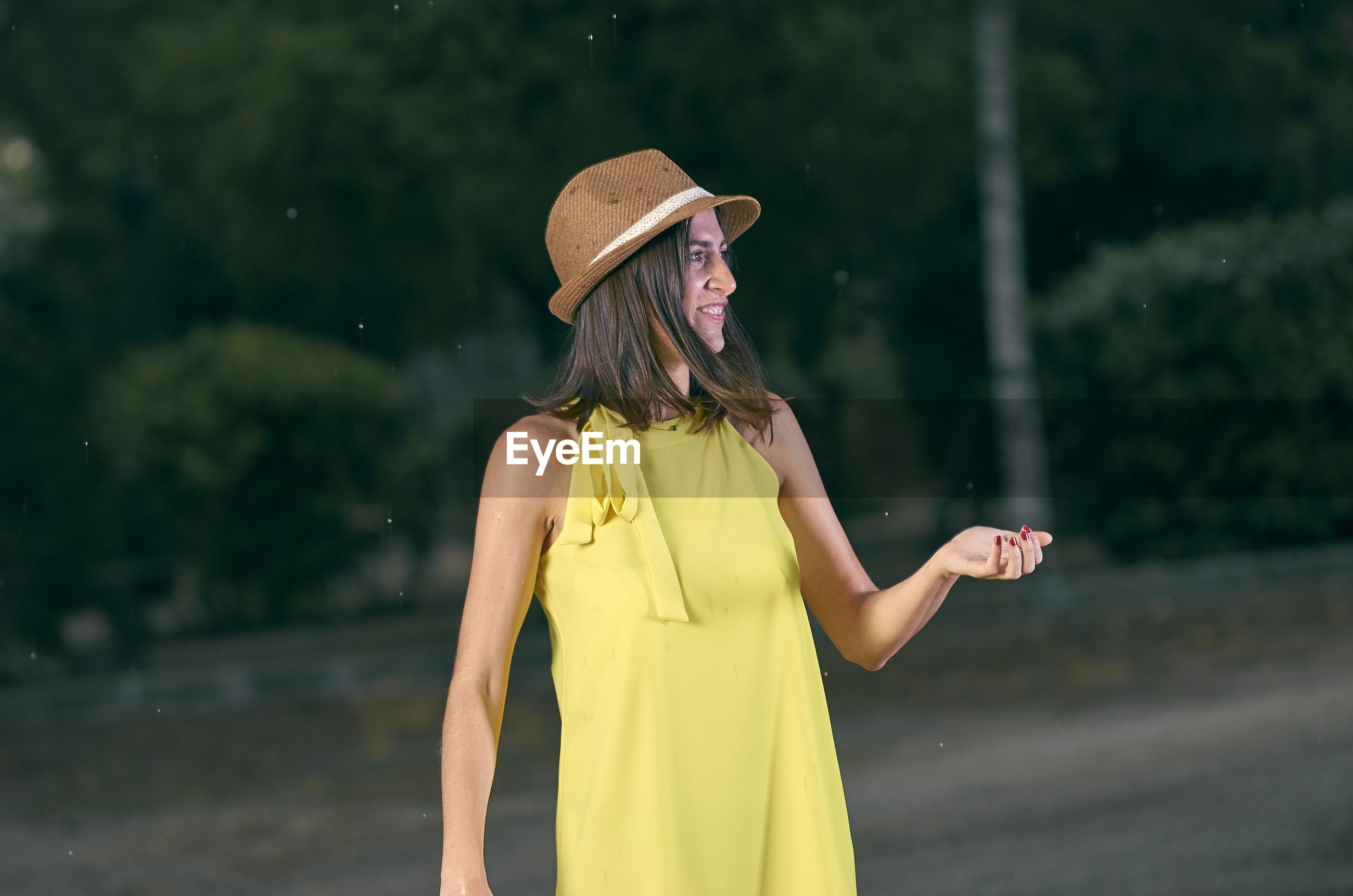 Woman wearing hat standing against trees on road