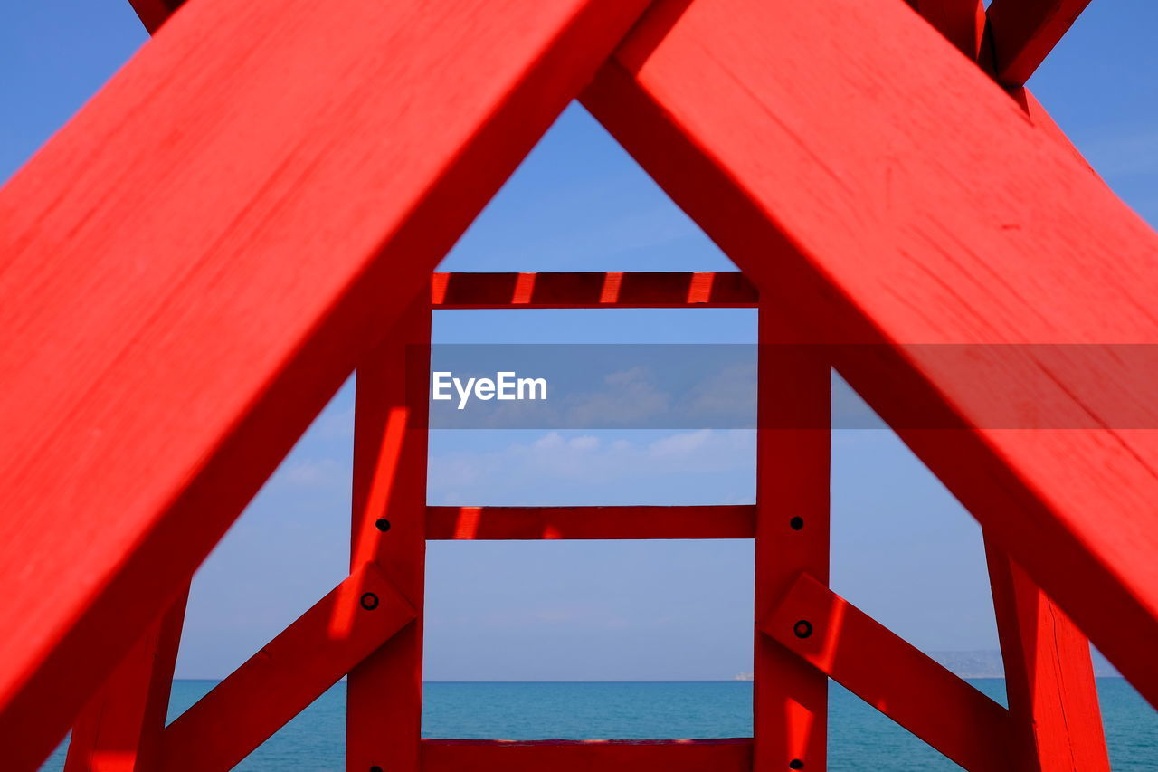 red, built structure, architecture, sky, no people, day, metal, nature, sunlight, bridge, clear sky, connection, blue, outdoors, bridge - man made structure, sea, focus on foreground, water, close-up, pattern, girder