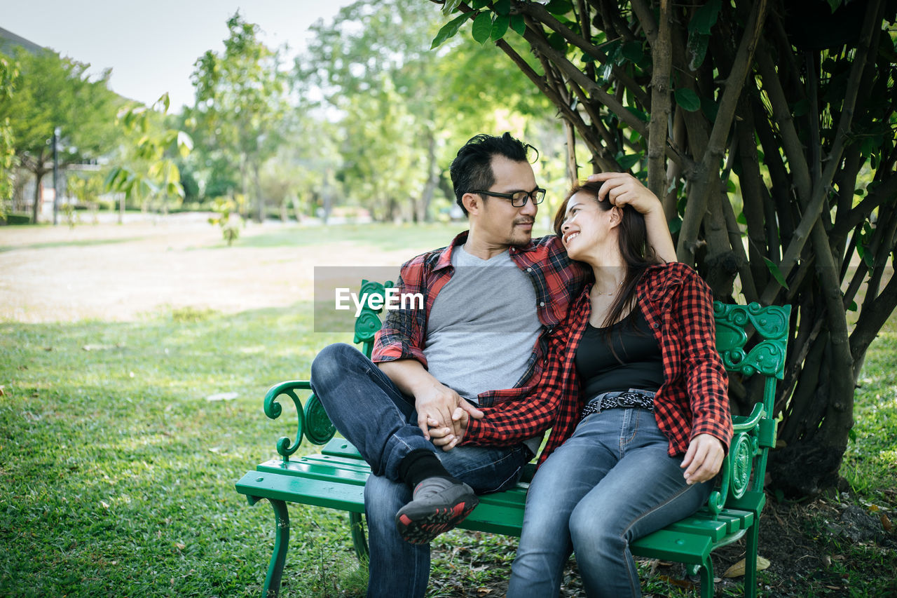 Couple relaxing on bench at park