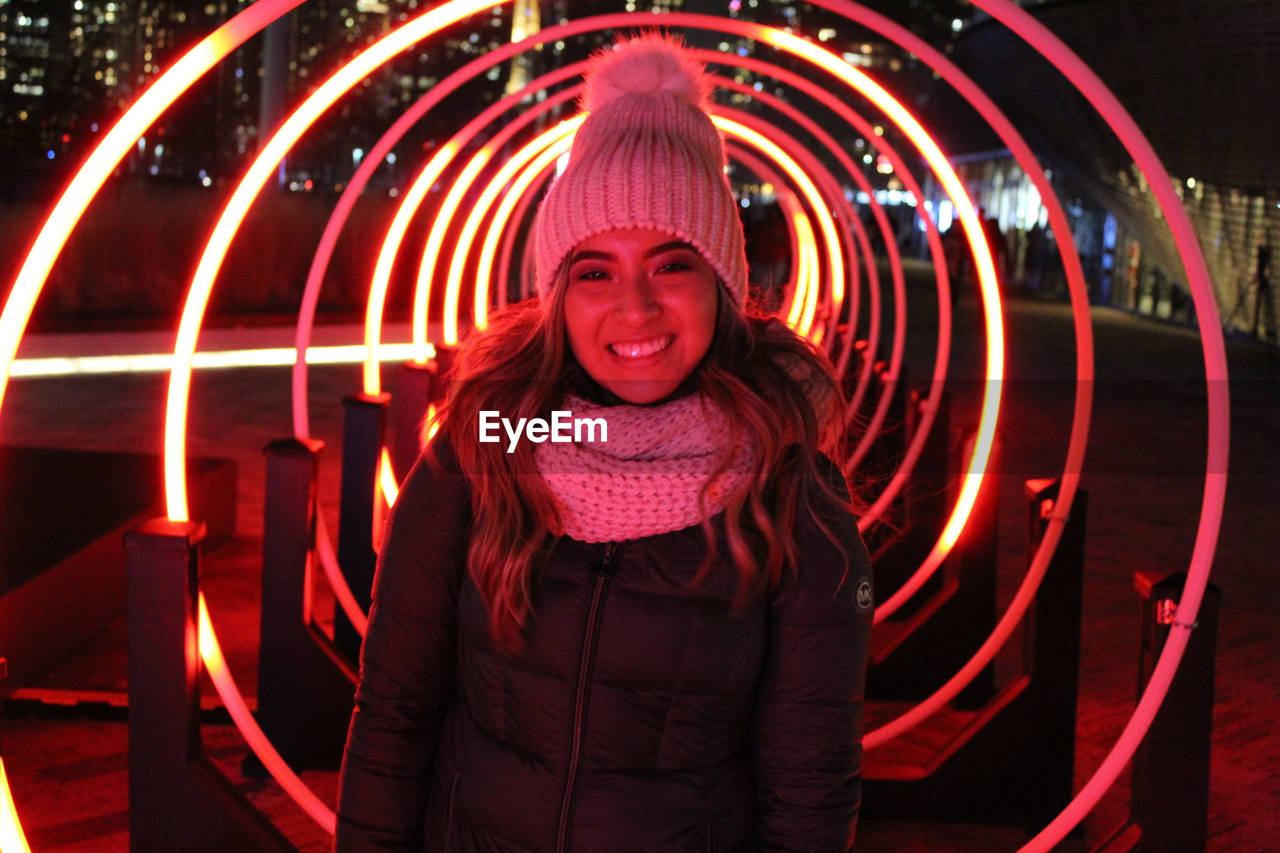 Portrait of smiling woman against illuminated built structure at night