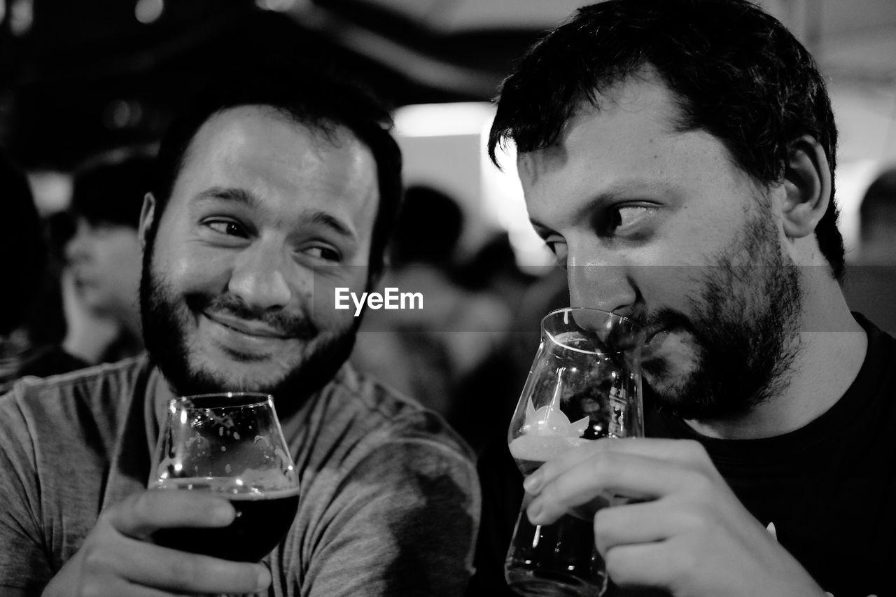 Smiling friends having beer in bar