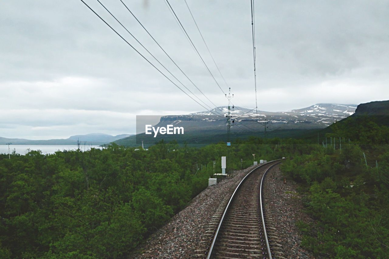 railroad track, transportation, cable, rail transportation, day, nature, electricity, power line, outdoors, no people, connection, beauty in nature, electricity pylon, sky, travel, railway track, the way forward, public transportation, landscape, scenics, mountain, tree