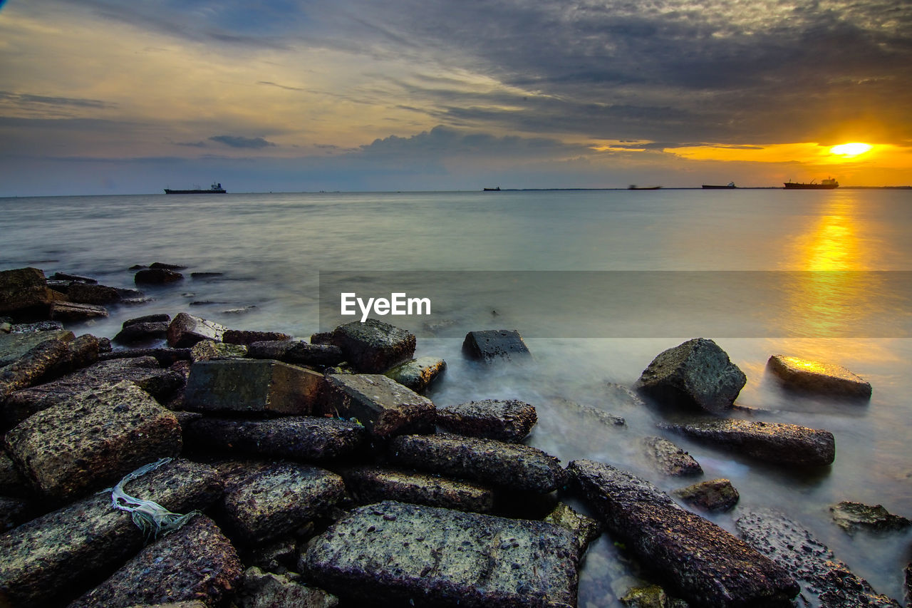 sky, sea, sunset, water, cloud - sky, scenics - nature, beauty in nature, solid, horizon over water, rock, tranquility, horizon, tranquil scene, rock - object, nature, no people, beach, land, idyllic, outdoors, rocky coastline