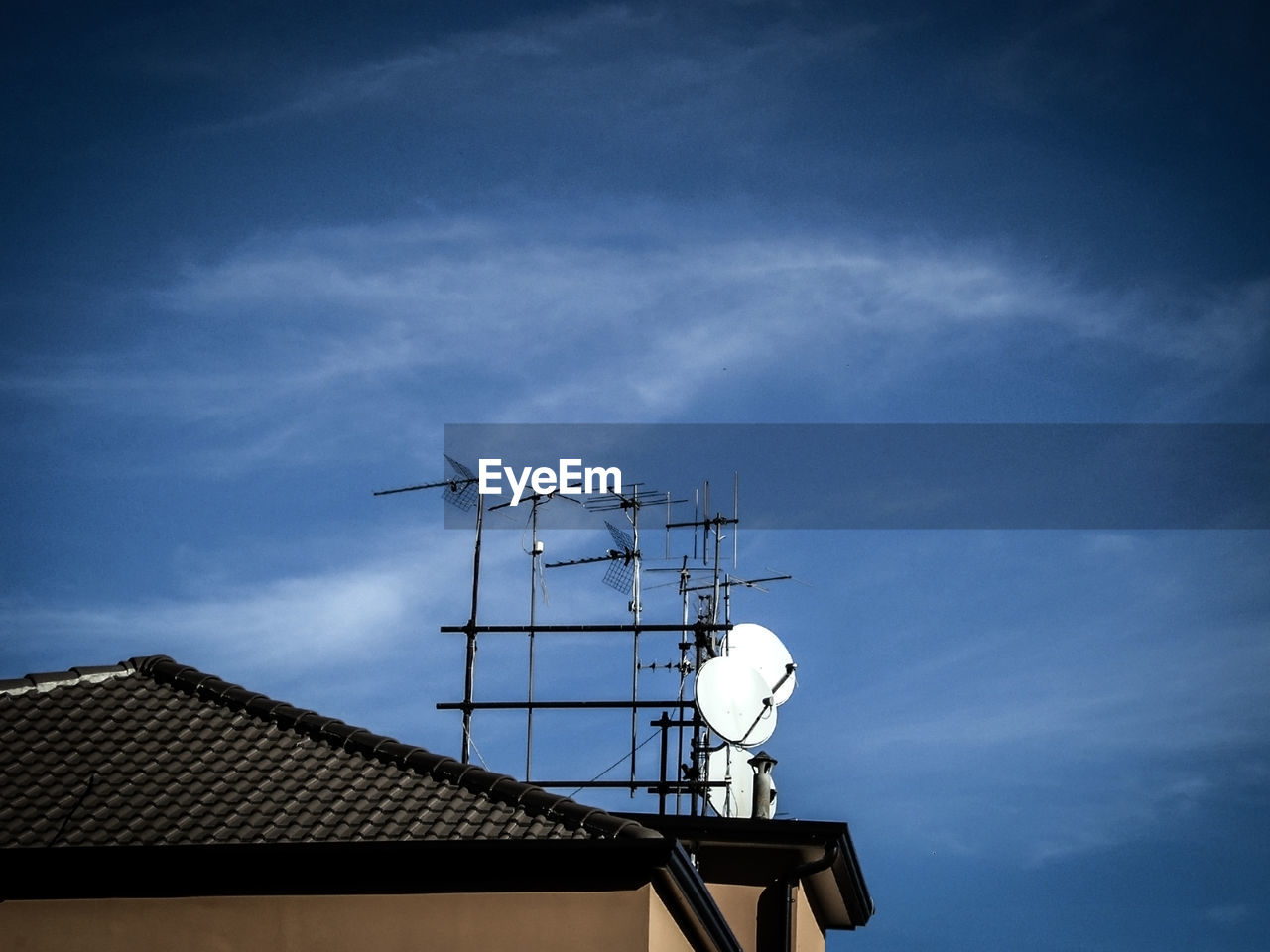 communication, technology, telecommunications equipment, antenna - aerial, architecture, built structure, connection, building exterior, roof, low angle view, television aerial, satellite dish, wireless technology, sky, day, outdoors, cloud - sky, global communications, no people, blue, tiled roof