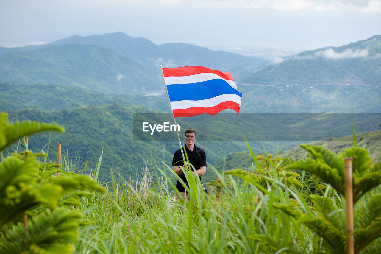 Man With Thai Flag Standing On Field Against Mountains