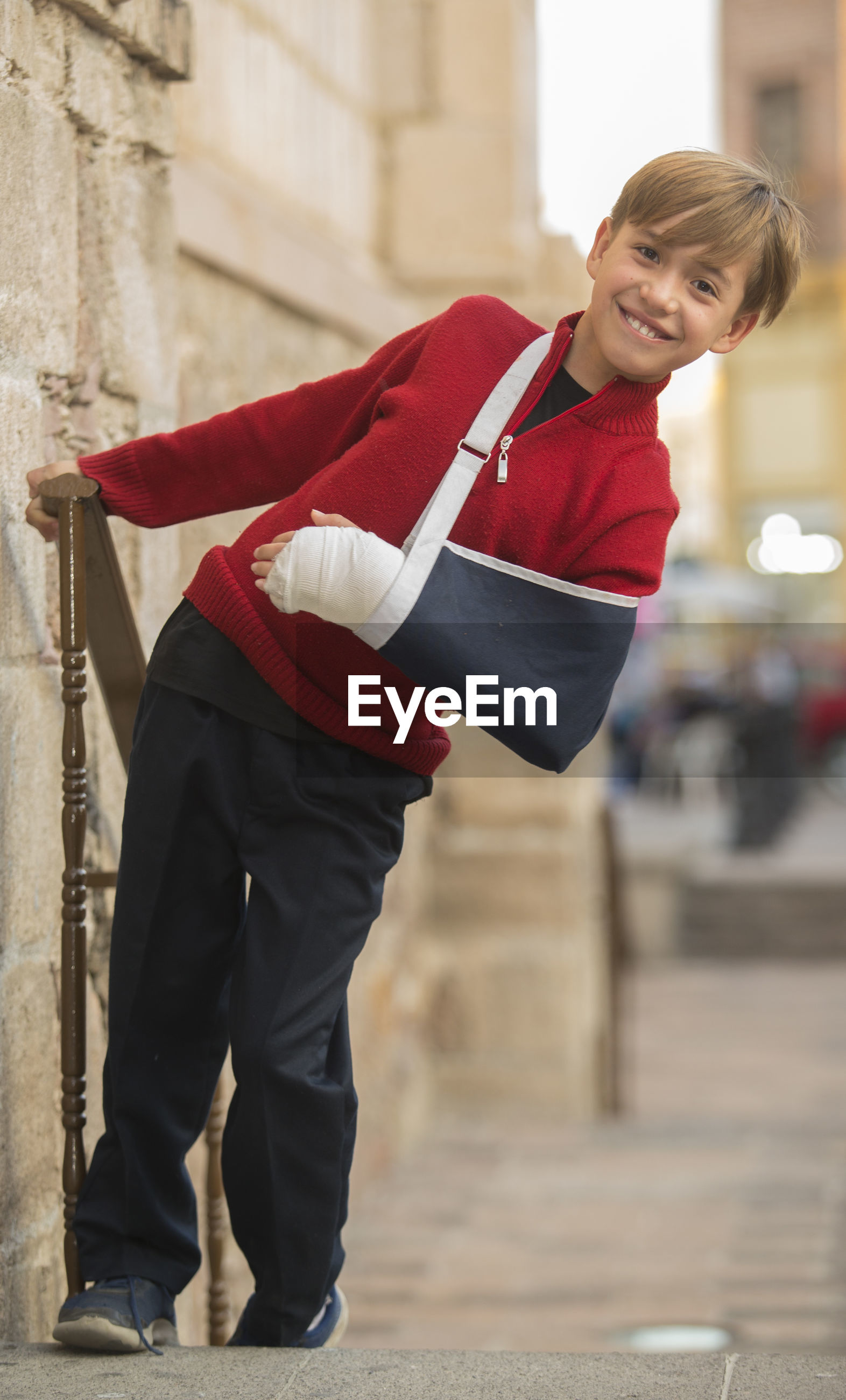 Portrait of smiling boy with orthopedic cast standing outdoors