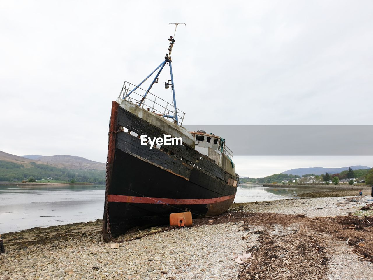 ABANDONED SHIP MOORED ON SHORE AGAINST SKY