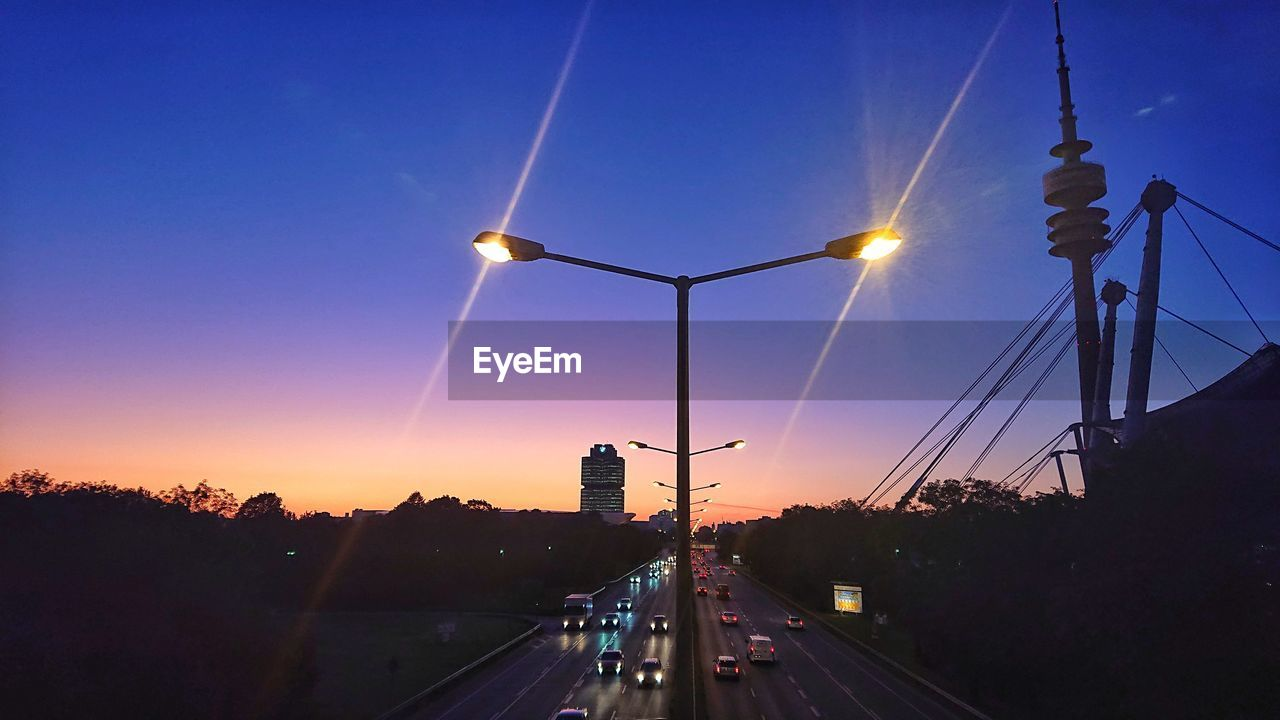 sky, transportation, street, street light, road, architecture, lighting equipment, illuminated, sunset, nature, built structure, connection, the way forward, direction, city, mode of transportation, no people, sun, car, lens flare, electricity, outdoors, bridge - man made structure, diminishing perspective