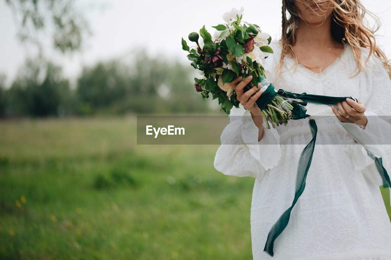 Midsection of woman holding bouquet while standing on field