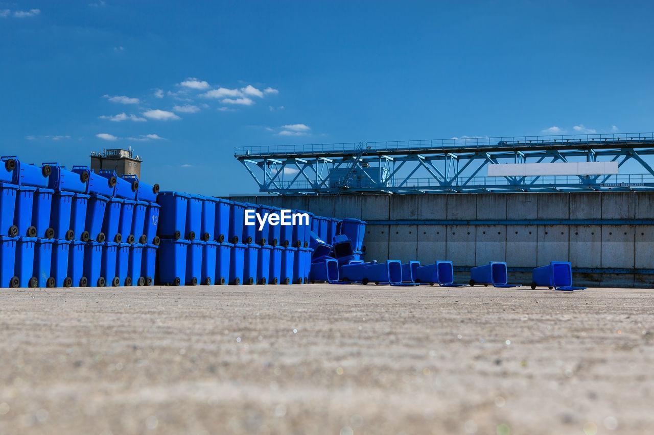 Blue Garbage Bins On Field Against Sky