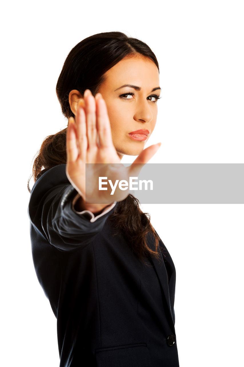 Portrait Of Businesswoman Gesturing Against White Background