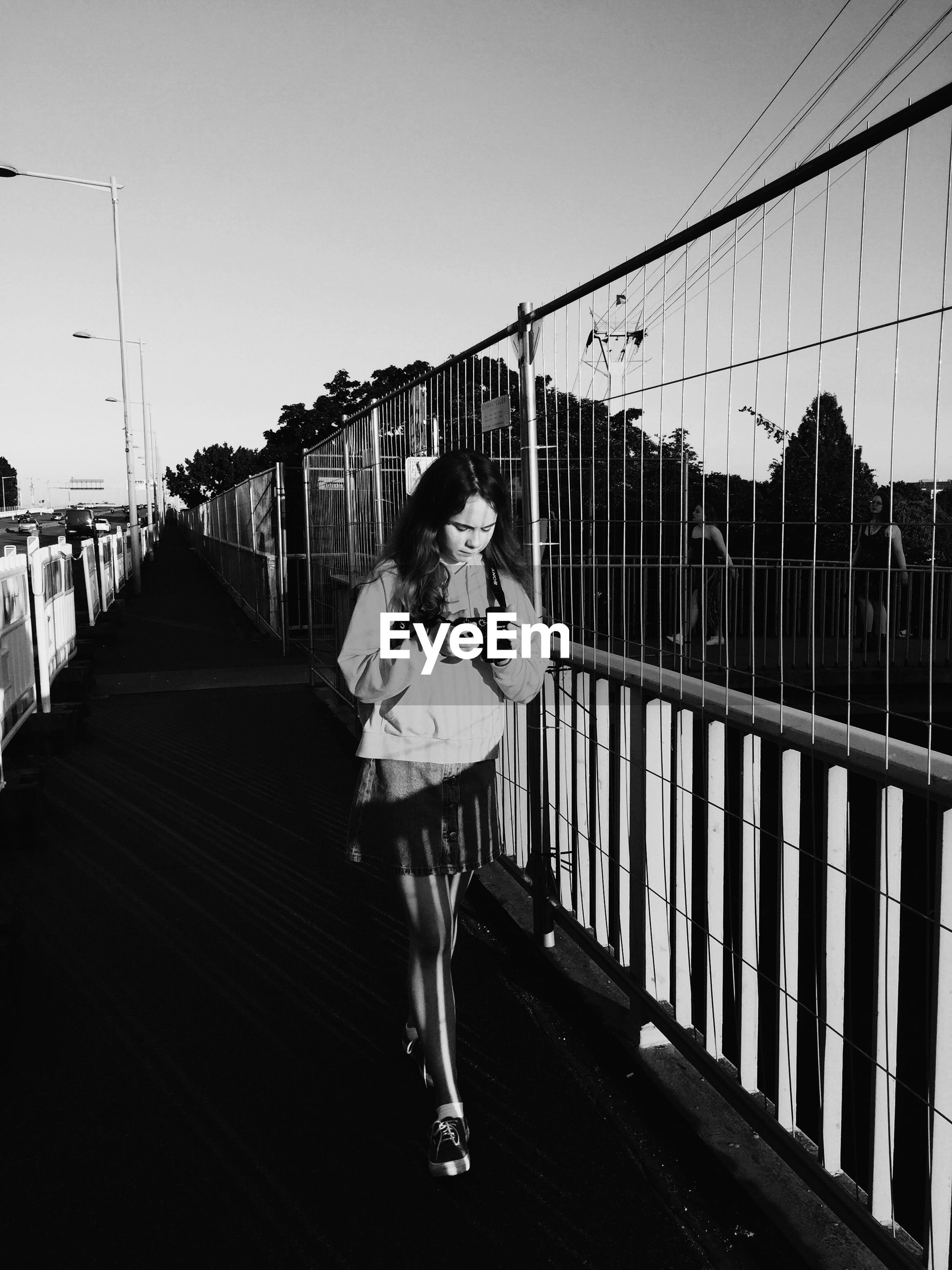 Teenage girl walking by railing on bridge in city