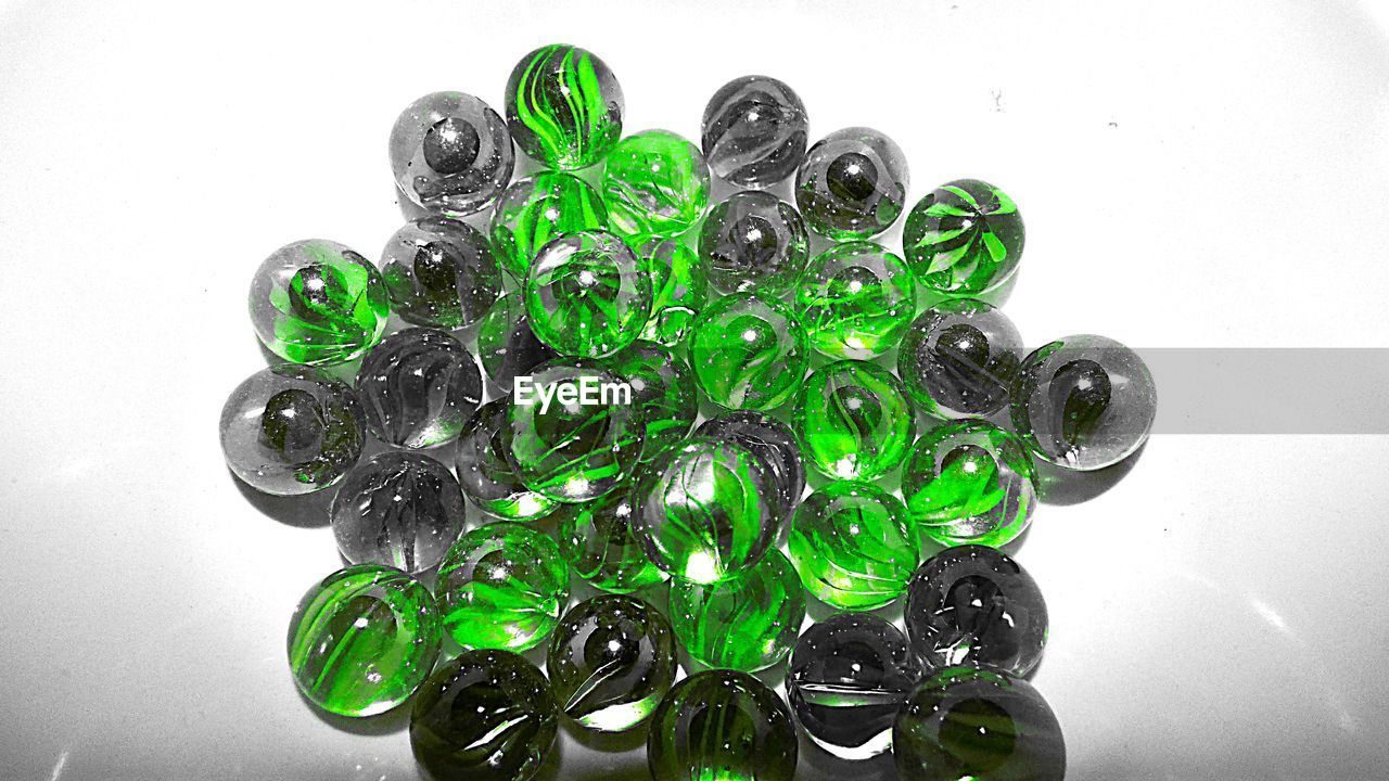 High angle view of green marbles arranged on white background