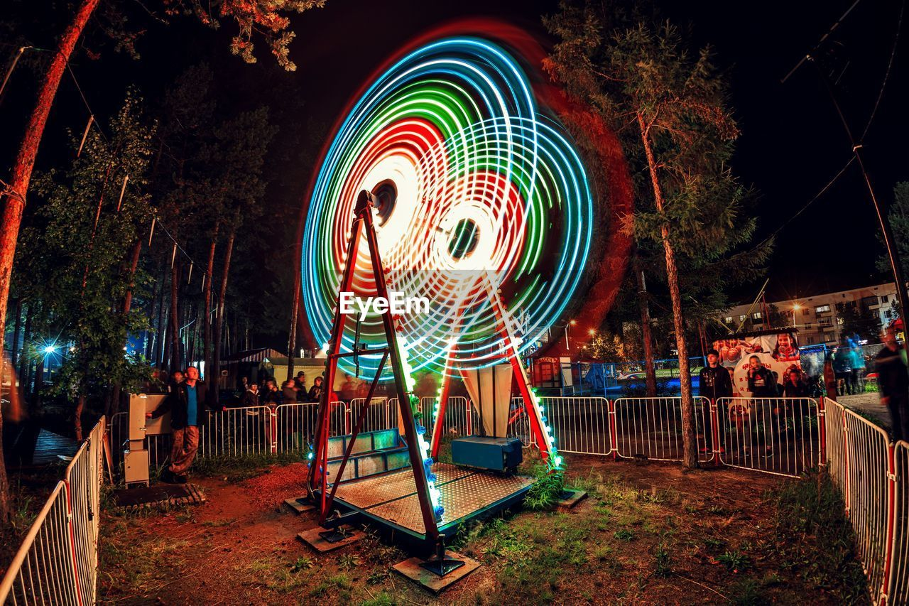 illuminated, night, multi colored, long exposure, arts culture and entertainment, amusement park ride, motion, amusement park, spinning, glowing, light painting, nature, blurred motion, ferris wheel, incidental people, leisure activity, creativity, tree, circle, outdoors