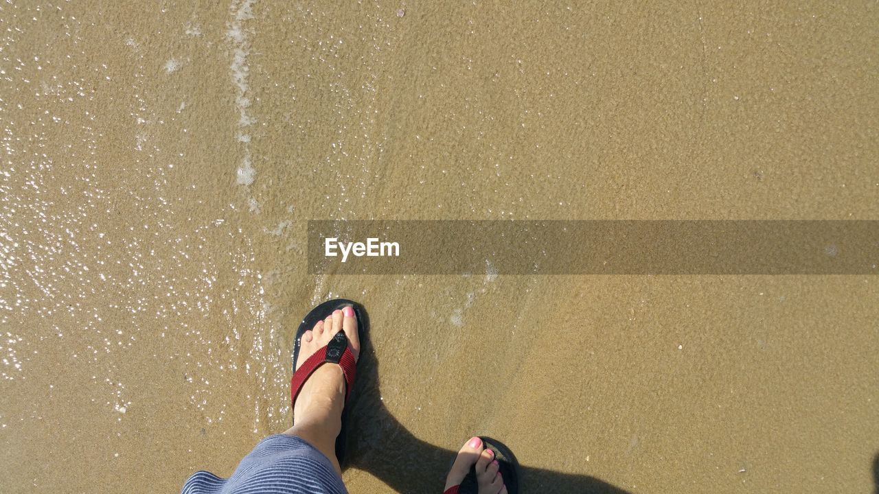 Low section of woman in red flip flops standing on wet sand beach