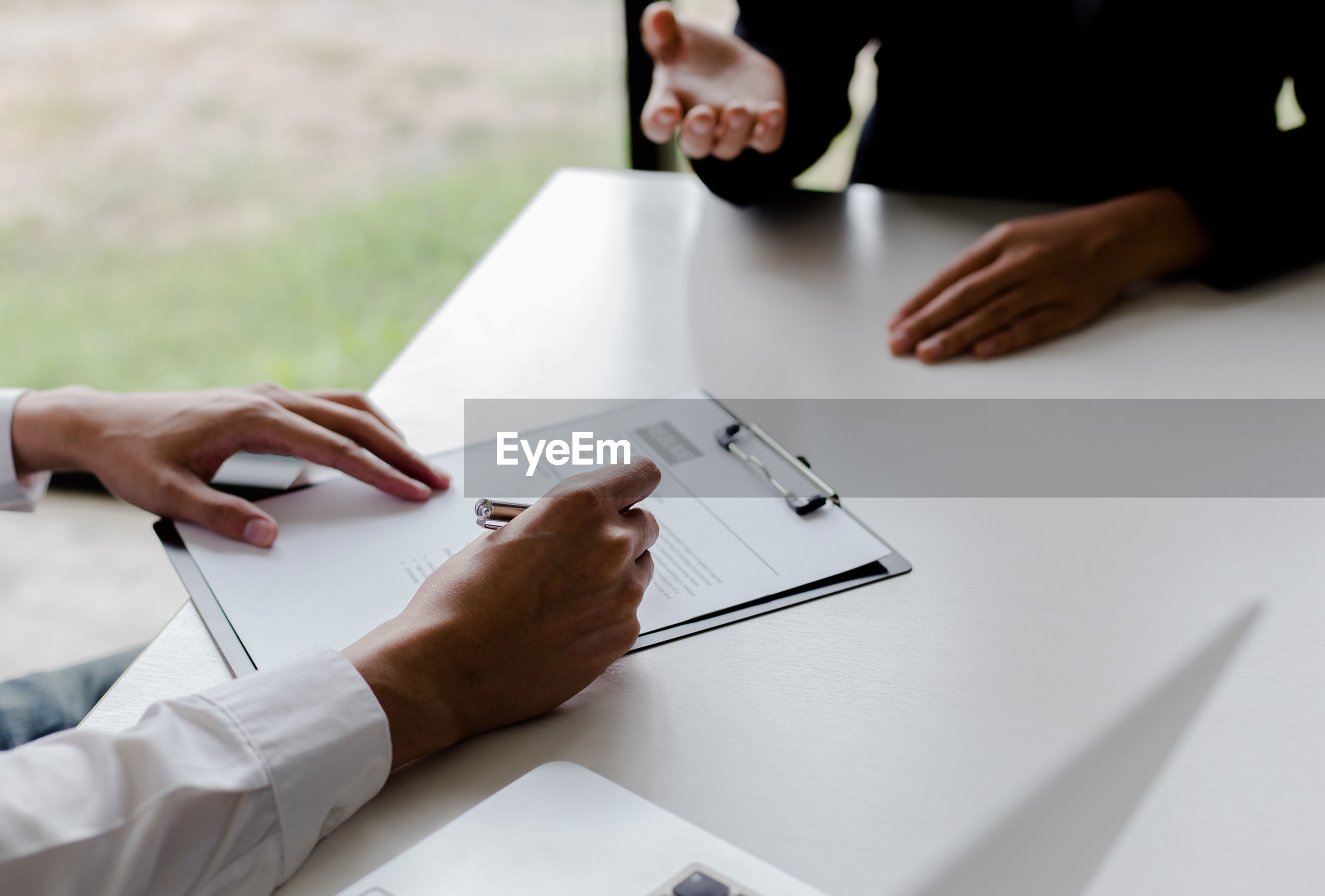 Cropped hands of businessman interviewing female candidate at desk in office
