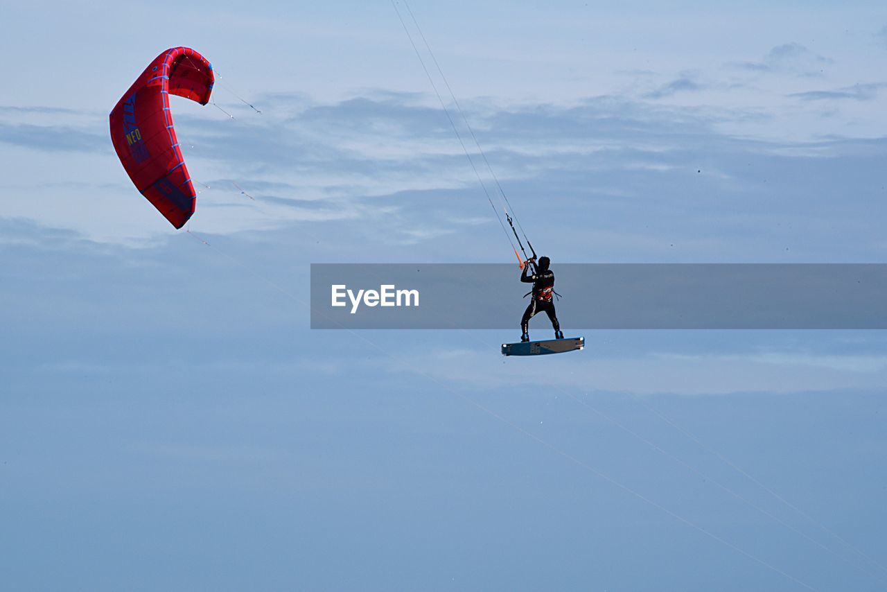 Low Angle View Of Man Kiteboarding Against Sky