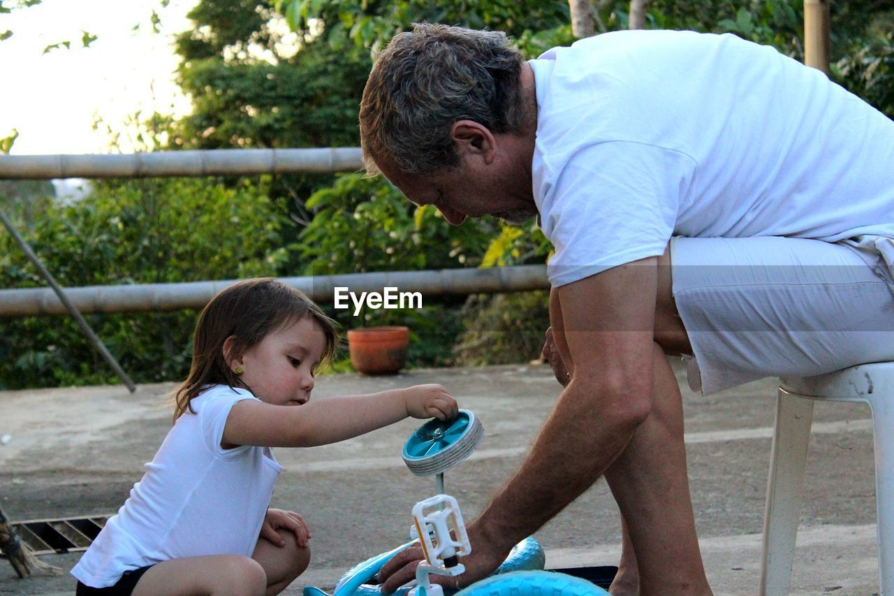 Side view of grandfather adjusting bicycle wheel with granddaughter in yard