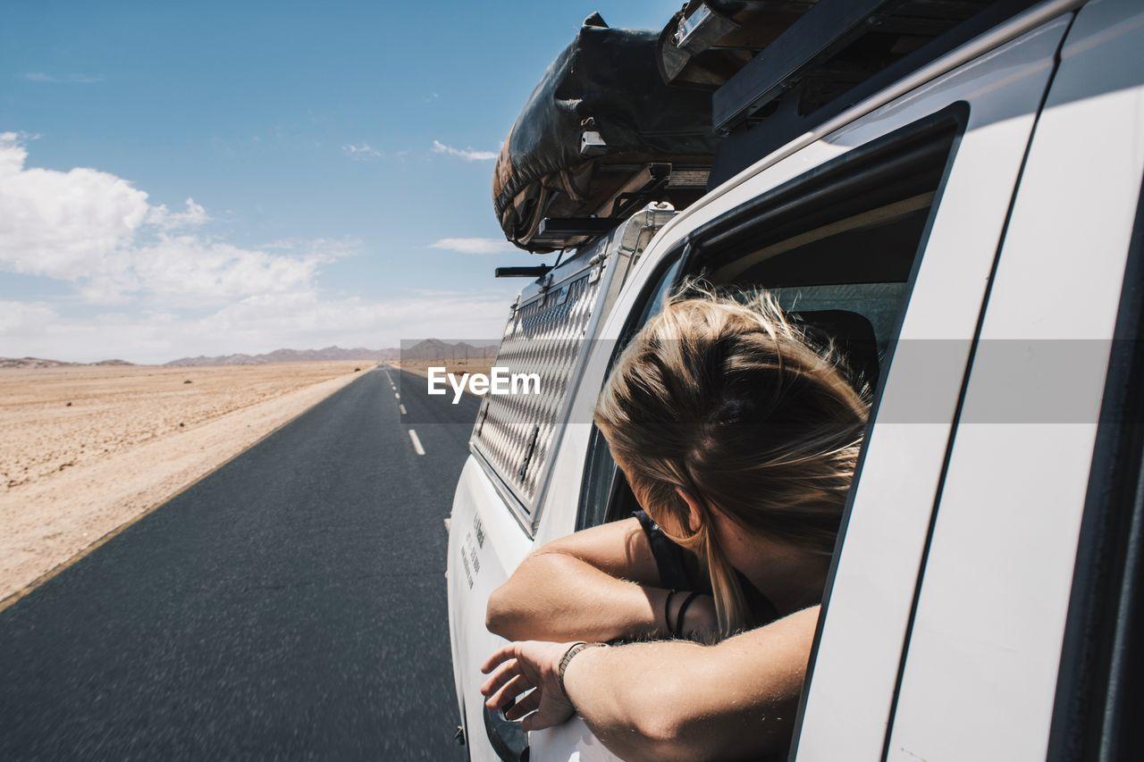 Woman Looking Through Car Window Against Sky