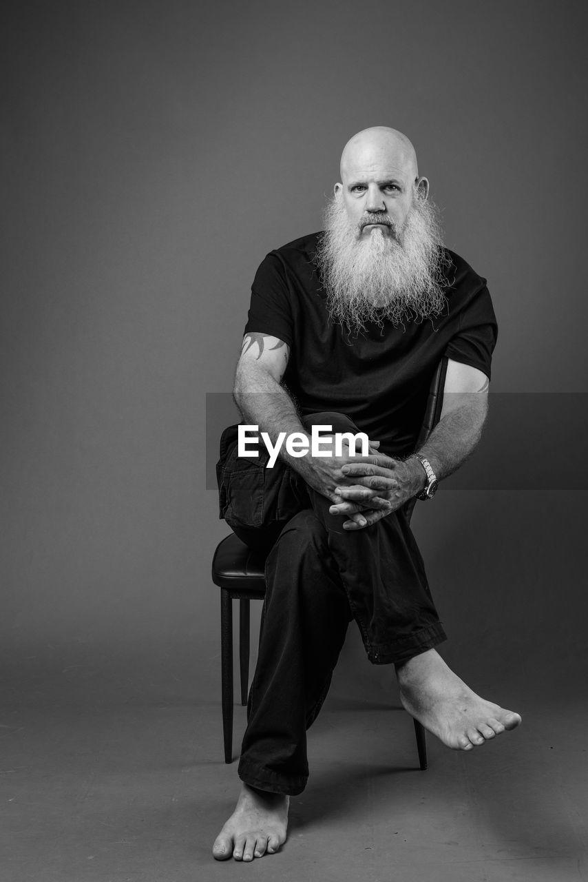 Portrait of man sitting against wall
