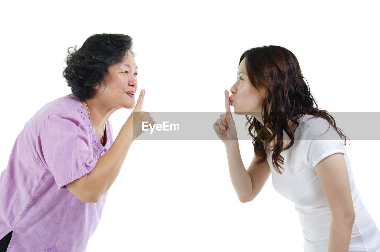Close-Up Of Mother And Daughter With Finger On Lips Against White Background