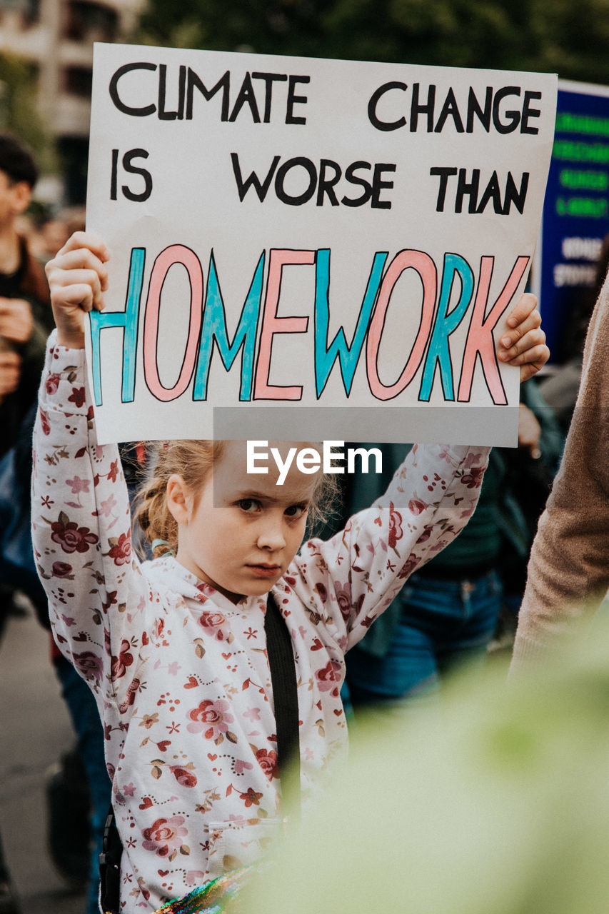 text, western script, communication, real people, childhood, front view, lifestyles, girls, holding, people, child, casual clothing, day, women, portrait, sign, females, incidental people, protest, innocence, message