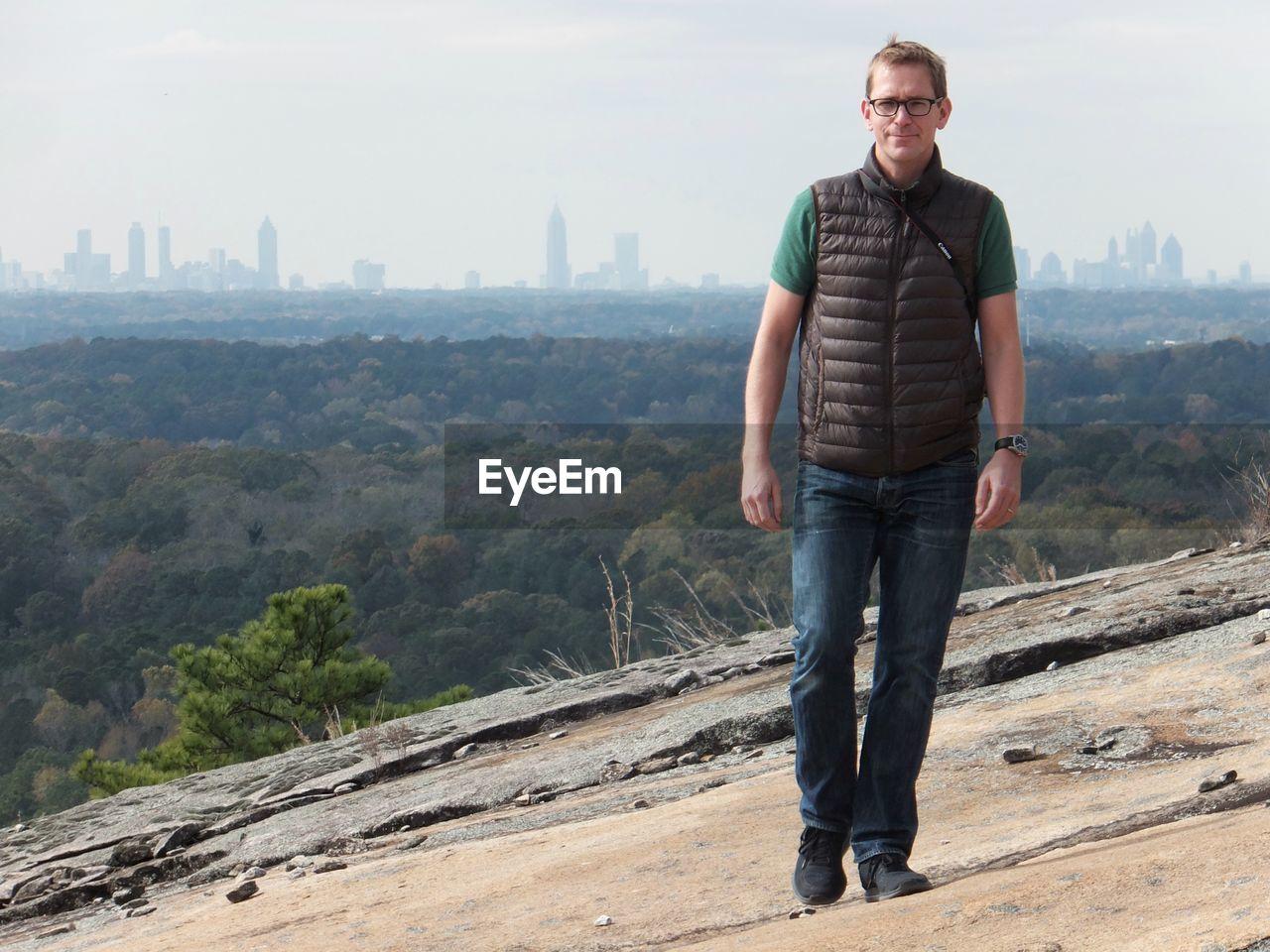 FULL LENGTH PORTRAIT OF MAN STANDING ON MOUNTAIN