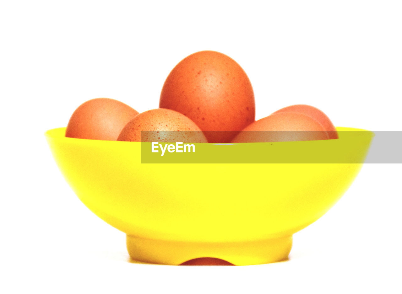 studio shot, white background, food, food and drink, wellbeing, healthy eating, freshness, egg, still life, indoors, cut out, group of objects, no people, close-up, raw food, orange color, bowl, fruit, medium group of objects, animal egg, ripe