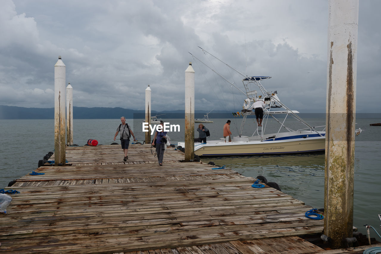 GROUP OF PEOPLE ON PIER OVER SEA AGAINST SKY