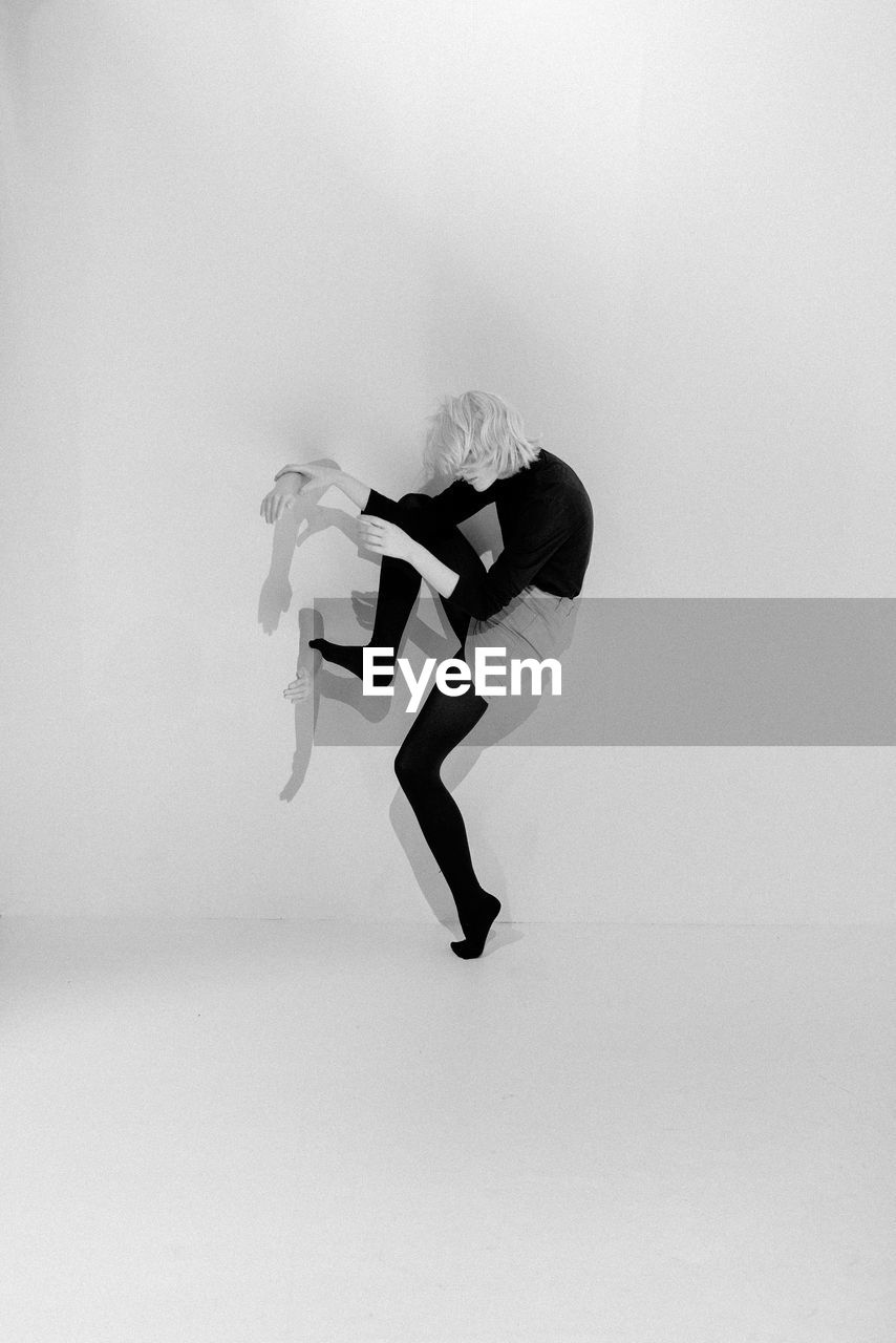 Woman Holding Mannequin Hand While Standing Over White Background