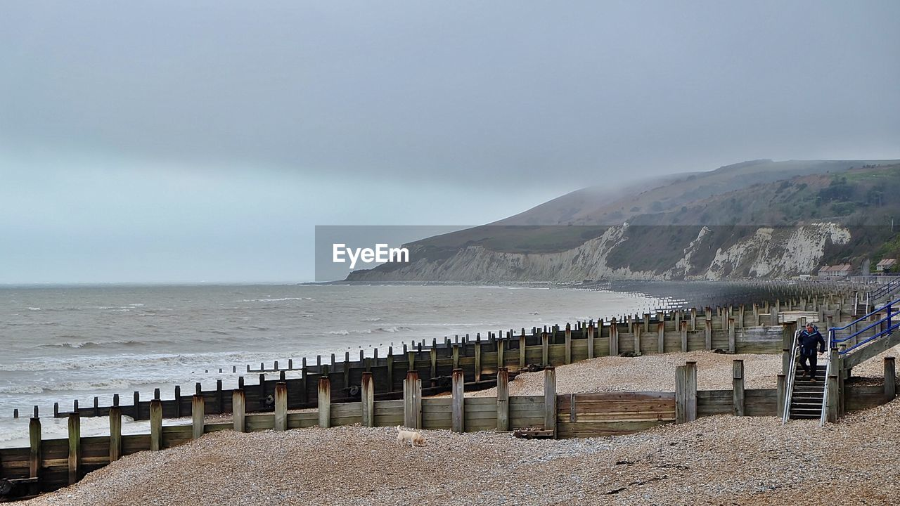 sea, beach, water, nature, scenics, beauty in nature, day, horizon over water, tranquil scene, outdoors, tranquility, sand, sky, mountain, travel destinations, real people, groyne