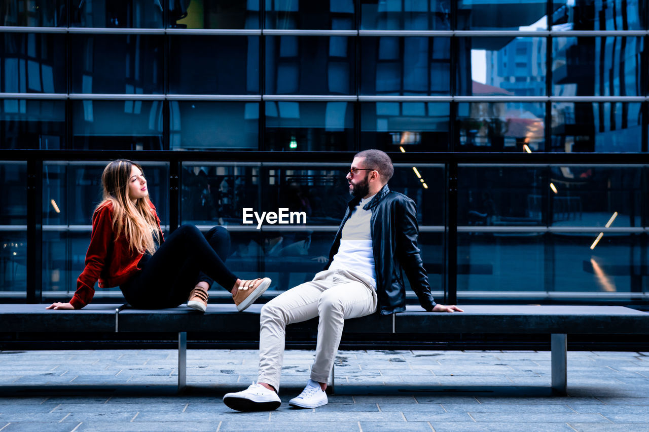 Man And Woman Sitting On Seat Against Building In City