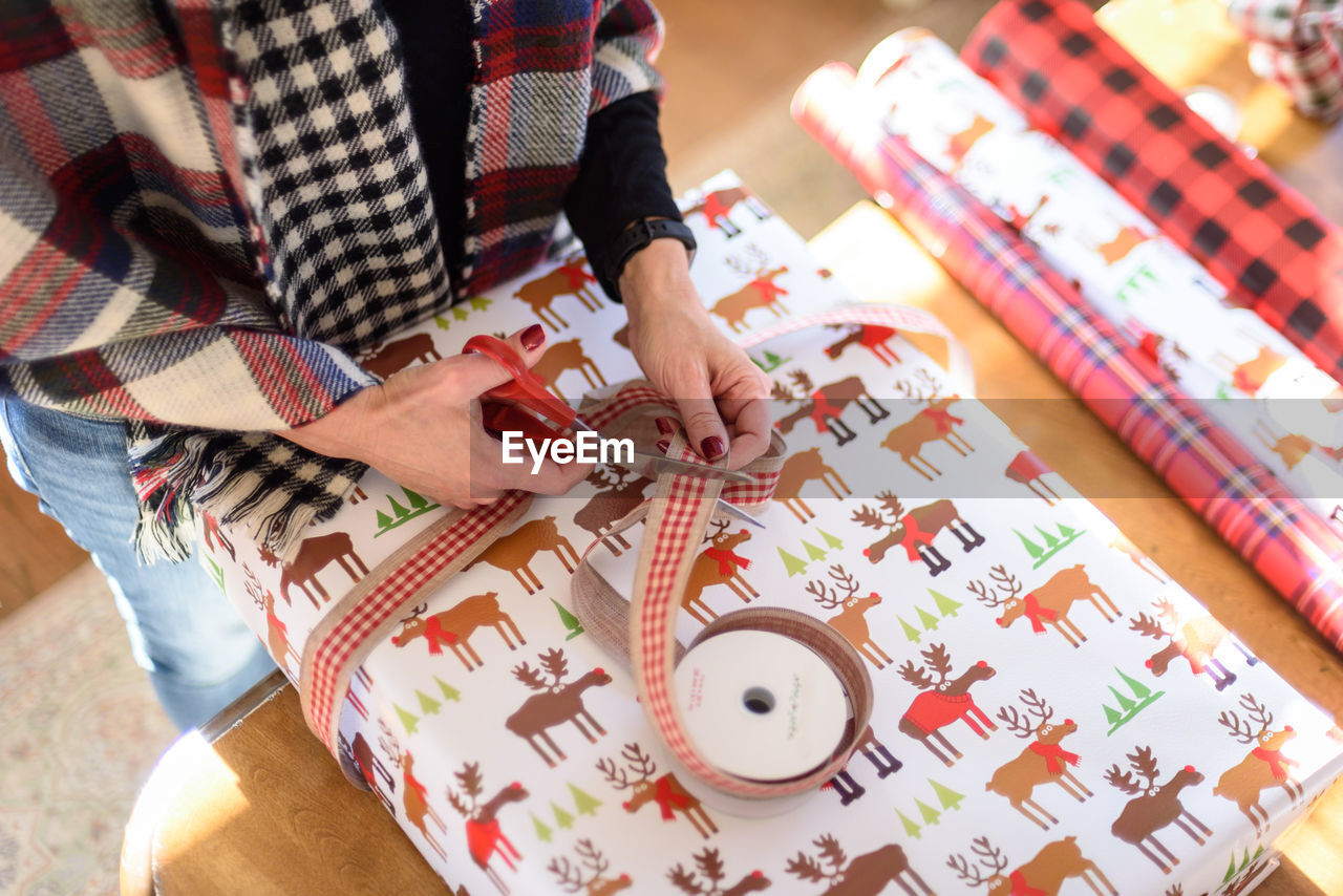 Midsection of woman wrapping gift at home