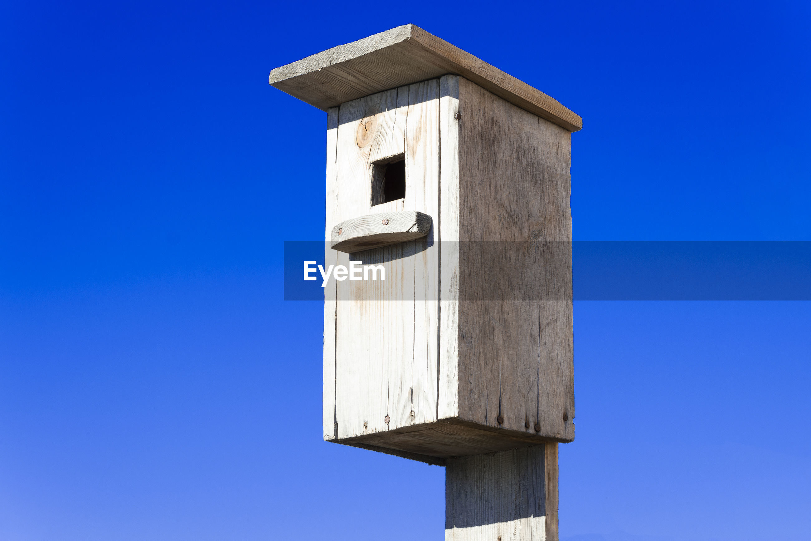 Low angle view of bird house against clear blue sky