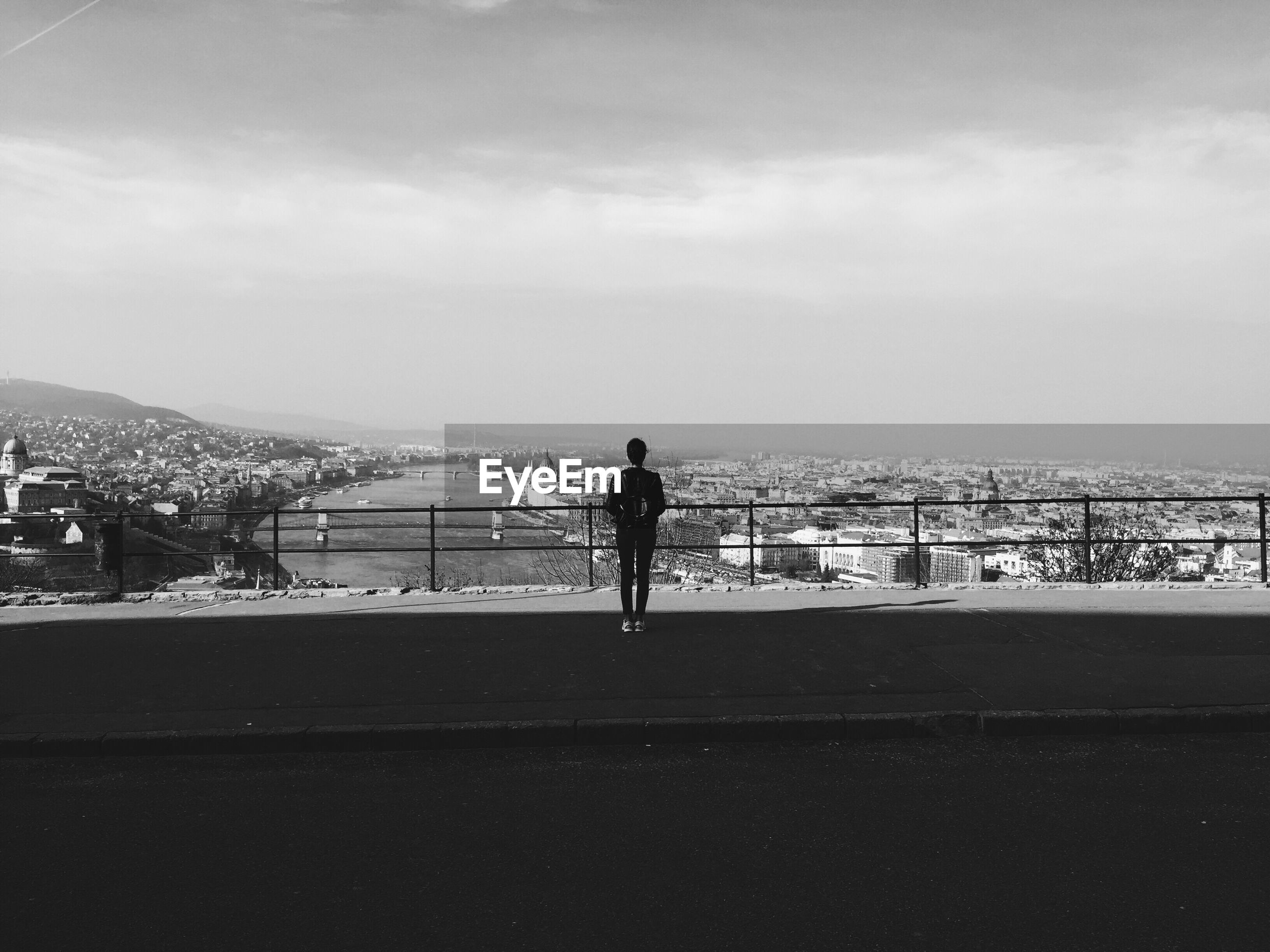 Rear view of woman standing on observation point by city against sky