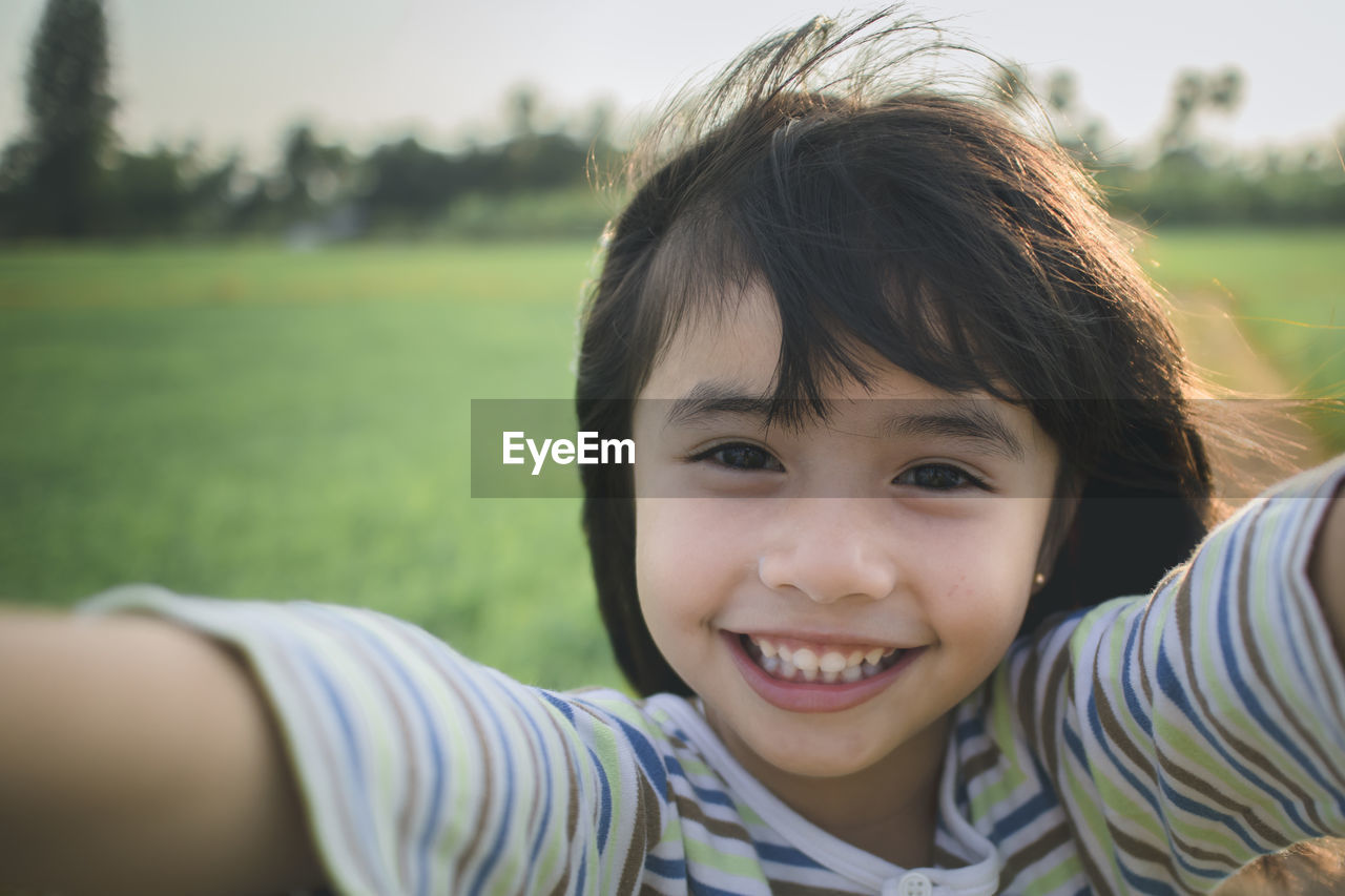 Portrait of cute smiling girl standing on grassy field