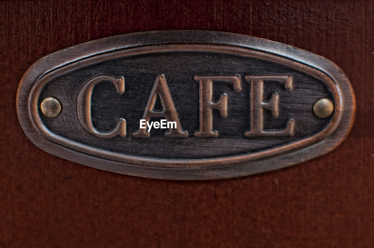 studio shot, text, indoors, food and drink, no people, western script, wood - material, close-up, food, drink, metal, brown background, brown, colored background, table, capital letter, coffee, refreshment, communication, celebration, wood grain, silver colored
