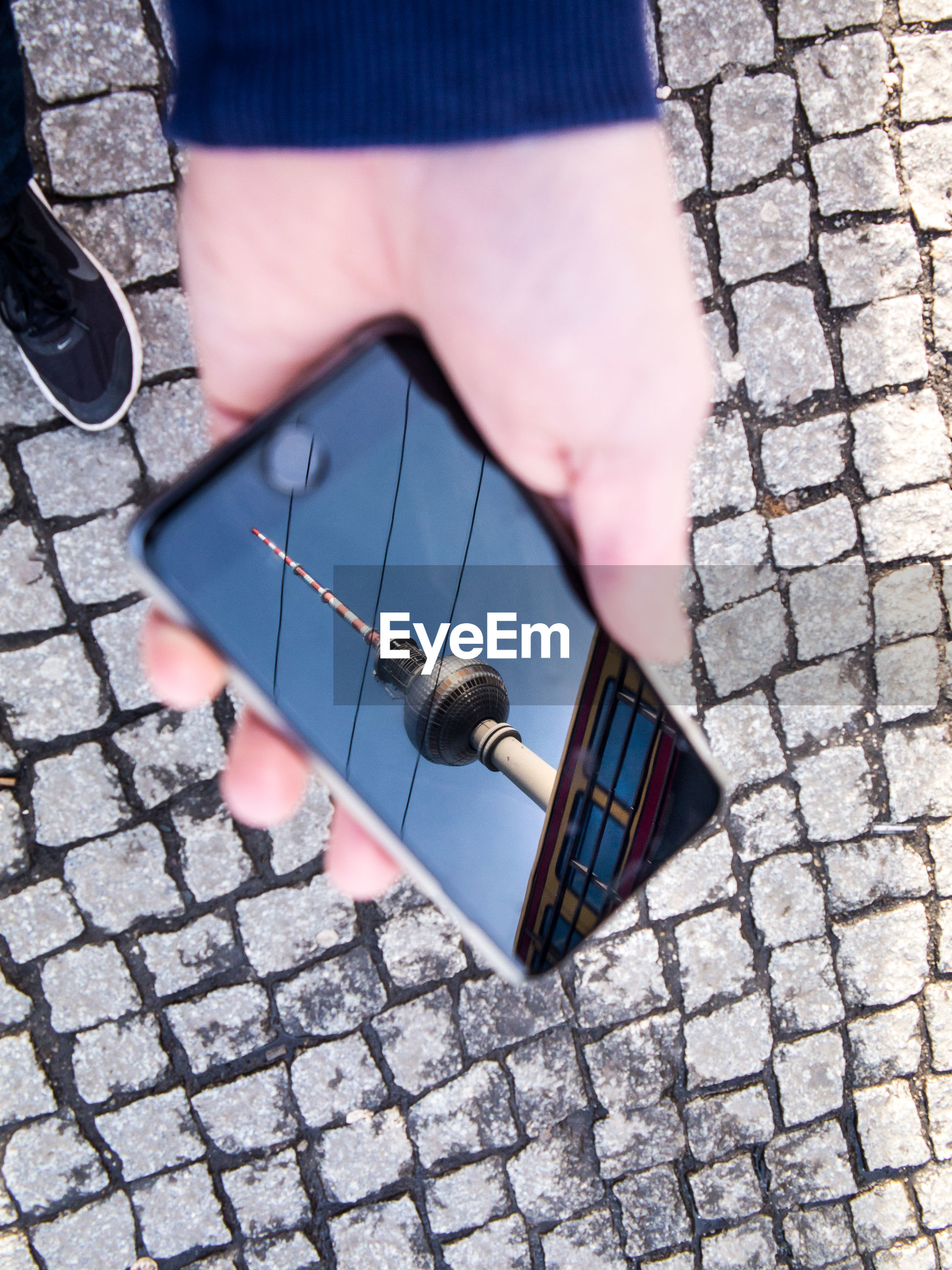Close-up of hand holding smart phone with fernsehturm on screen