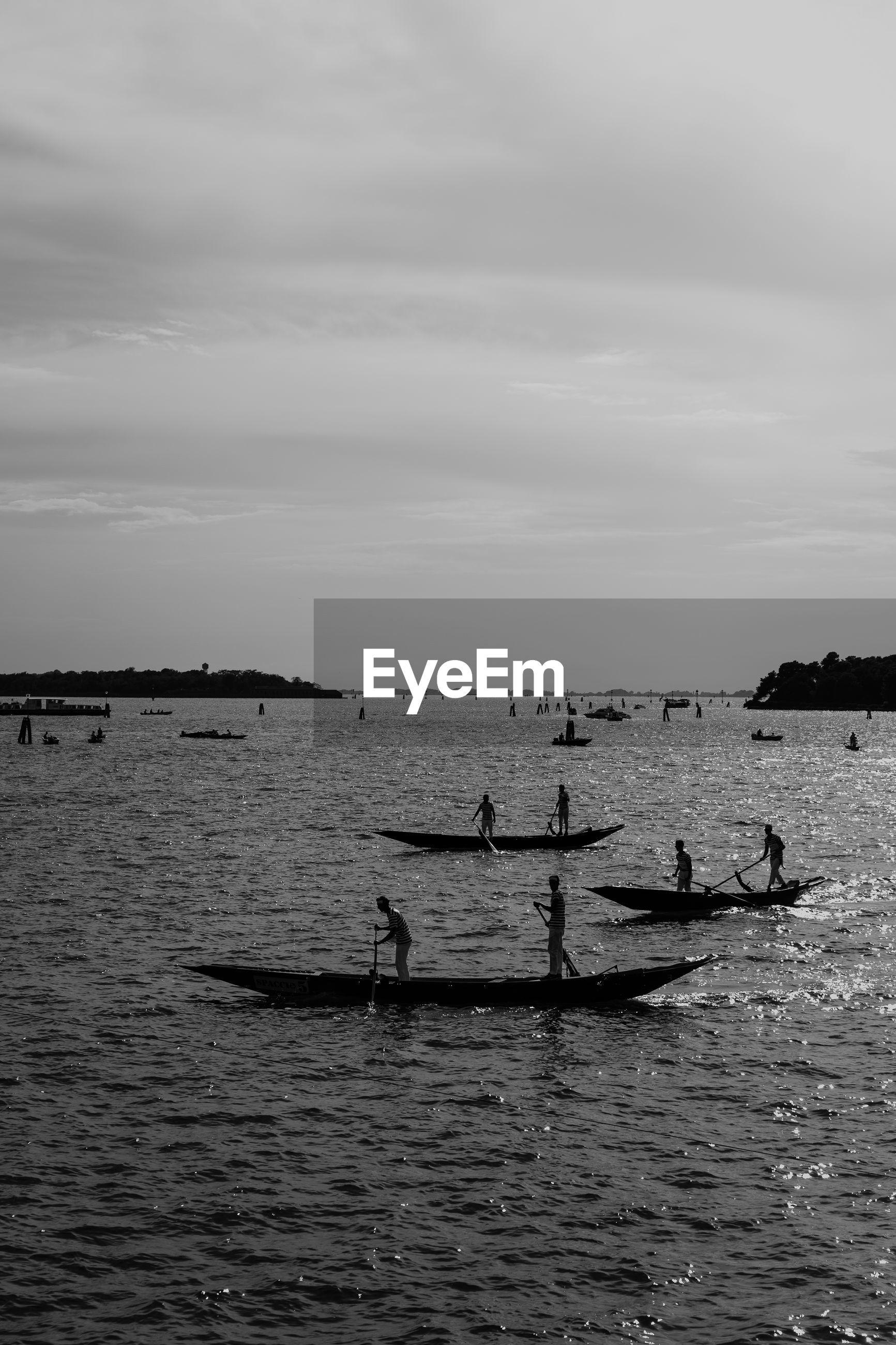People rowing in sea against sky